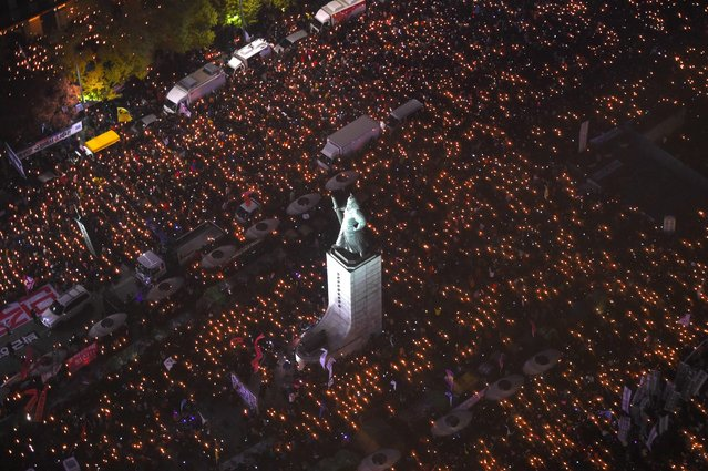 Protesters hold candles during an anti-government rally in central Seoul on November 12, 2016.  Tens of thousands of men, women and children joined one of the largest anti-government protests seen in Seoul for decades on November 12, demanding President Park Geun-Hye's resignation over a snowballing corruption scandal. (Photo by Jung Yeon-Je/AFP Photo)
