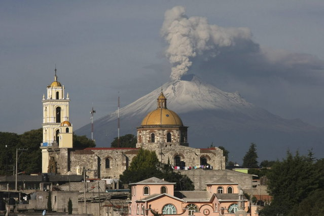 The main church in the town of San Damian Texoloc, Mexico stands in front of the Popocatepetl volcano as is spews ash and vapor early Tuesday, July 9, 2013. Last Saturday, Mexico's National Center for Disaster Prevention raised the volcano alert from Stage 2 Yellow to Stage 3 Yellow, the final step before a Red alert, when possible evacuations could be ordered after the Popocatepetl volcano spit out a cloud of ash and vapor 2 miles (3 kilometers) high over several days of eruptions. (Photo by J. Guadalupe Perez/AP Photo)