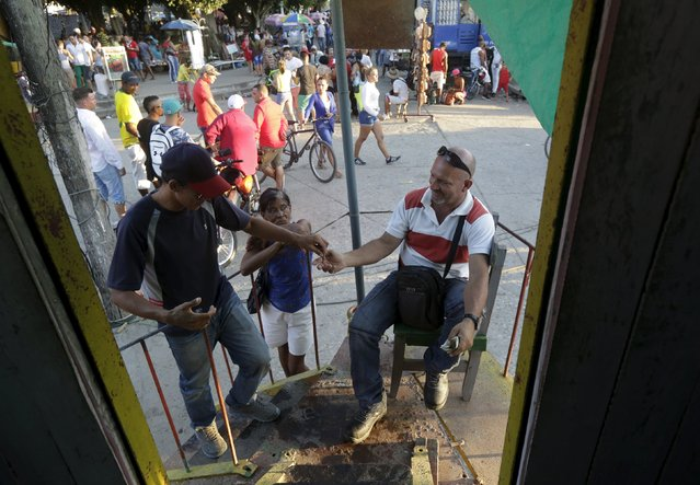 Mario Munoz receives payment from a man to use his mobile ecological bathroom in Vertientes, Camaguey province November 13, 2015. Munoz, self-employed, is the owner of the mobile eco-bathroom. For neighborhood events, he rents a truck and opens the bathroom to the public for a small fee. (Photo by Enrique de la Osa/Reuters)