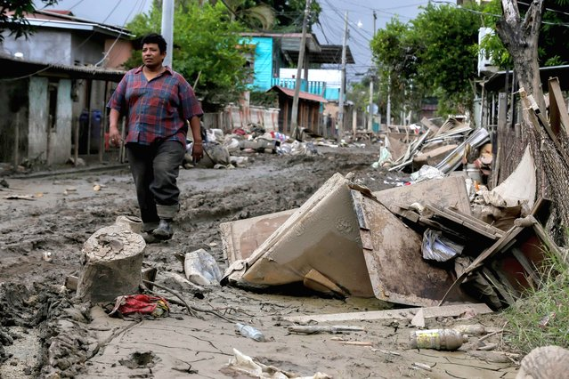 "A man walks along a damaged street after the passage of Hurricane Eta in La Lima, Cortes, Honduras, on November 16, 2020 as Hurricane Iota – upgraded to Category 5 – moves over the Caribbean towards the Nicaragua-Honduras border. Hurricane Iota strengthened into a ""catastrophic"" Category 5 hurricane and was set to slam into Central America late Monday, threatening areas devastated by a powerful storm just two weeks ago, the US National Hurricane Center (NHC) warned. (Photo by Wendell Escoto/AFP Photo)"