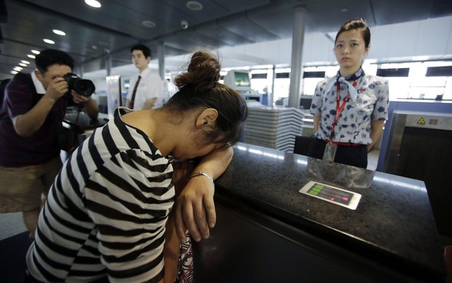 An unidentified family member of one of two Chinese students killed in a crash of Asiana Airlines' plane on Saturday, cries at the Airlines' counter as she and other family members check in a flight to San Francisco at Pudong International Airport in Shanghai, China, Monday, July 8, 2013. The Asiana flight crashed upon landing Saturday, July 6, at San Francisco International Airport, and the two of the 307 passengers aboard were killed. (Photo by Eugene Hoshiko/AP Photo)