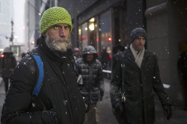 People walk along 42nd St at Grand Central Terminal as it snows in the Manhattan borough of New York January 26, 2015. (Photo by Carlo Allegri/Reuters)