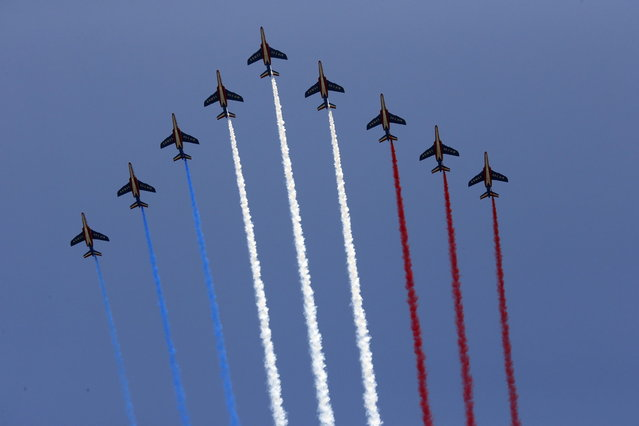 Nine alphajets from the French Air Force Patrouille de France releasing trails of red, white and blue smoke, colors of French national flag, fly during the traditional Bastille day military parade on the Champs Elysee in Paris July 14, 2013. (Photo by Benoit Tessier/Reuters)