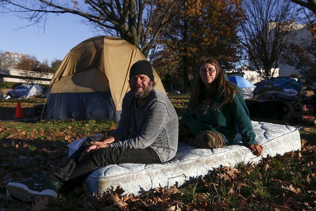 "Clyde Burgit and his wife Helen, who have been at the camp for two weeks, sit on a mattress near their tent by the Watergate and Whitehurst Freeway in Washington D.C., November 16, 2015. ""Everybody looks out for everybody, this was great and everybody gets along"", Clyde said. On November 20, 2015 the residents were evicted from the area, according to local reports. (Photo by Shannon Stapleton/Reuters)"