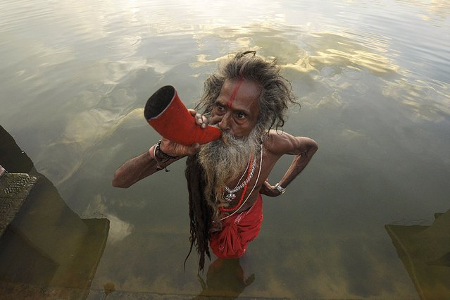 """An Indian """"sadhu"""" – holy man' blows a buffalo horn on the eve of the traditional Kharchi Puja festival at Agartala, the capital of northeastern state of Tripura, on July 16, 2013. (Photo by Arindam Dey/AFP Photo)"""