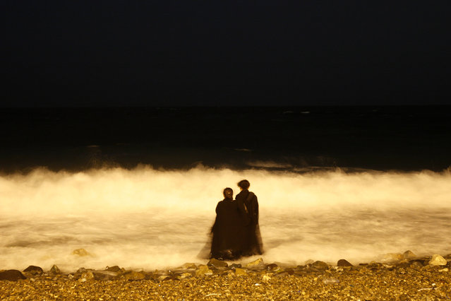 In this Tuesday, December 26, 2007 file photo, two veiled Saudi women enjoy the Red Sea at night, in Jiddah, Saudi Arabia. A growing number of Saudi women are remaining single through their 20s and into their 30s as they pursue their ambitions, sending ultraconservatives into a panic. (Photo by Hasan Sarbakhshian/AP Photo)