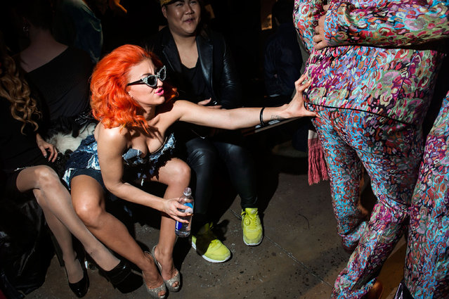 """A woman jokes and grabs another attendee of The Blonds fashion show at Milk Studios. Mercedes-Benz Fashion Week, New York City, Fall 2013. From the series """"Fashion Lust"""". (Photo by Dina Litovsky)"""