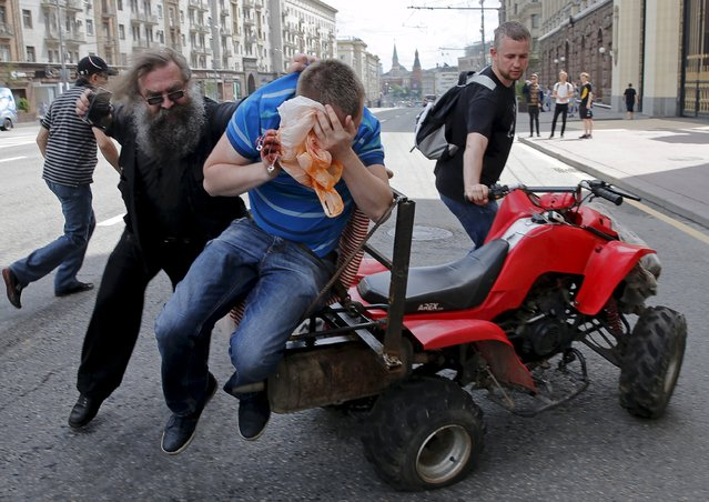 Anti-gay protesters attack a gay rights activist during an LGBT community rally in central Moscow, Russia, May 30, 2015. (Photo by Maxim Shemetov/Reuters)