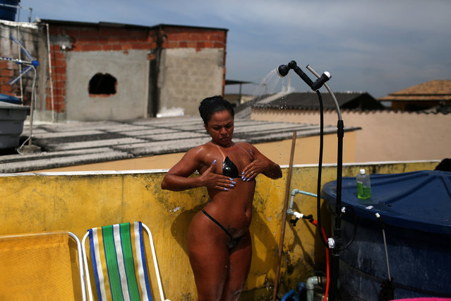 """A woman wearing their masking tape bikinis, takes a shower to refresh herself during sunbathing to have the perfect bikini mark (""""marquinha"""" in Portuguese), on a terrace at the Erika Bronze spa in Rio de Janeiro, Brazil, November 22, 2016. (Photo by Pilar Olivares/Reuters)"""