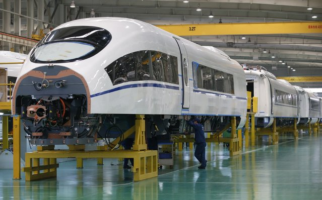 An employee works on a final assembly line for CRH380B, a high speed train model, at China CNR's Tangshan Railway Vehicle's factory in Tangshan, Hebei province, February 11, 2015. China CNR, one of the country's top trainmakers, said it was interested in buying foreign rail-linked technologies as China seeks to export its high-speed trains and rail expertise. (Photo by Kim Kyung-Hoon/Reuters)