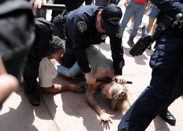 A police officer pins a woman down during confrontations with protesters, including Black Lives Matter and White Lives Matter activists and with at least a half a dozen arrested, in Huntington Beach, California, U.S., April 11, 2021. (Photo by David Swanson/Reuters)
