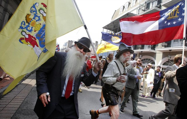 Chris Porrovecchio of Kendall Park, New Jersey ,left, carries the New Jersey state flag during a parade through the French Quarter kicking off the fourth annual Just For Men National Beard and Moustache Championships Saturday, September 7, 2013 in New Orleans. Contestants competed in 18 different categories including Dali, full beard natural and sideburns.  (Photo by Susan Poag/AP Photo)
