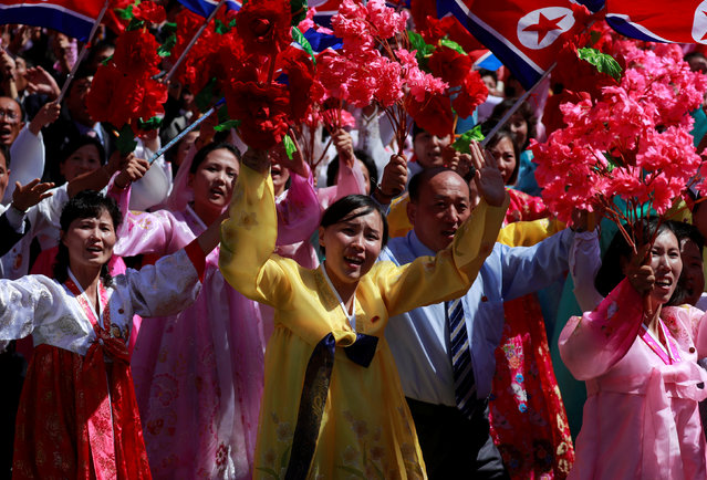 People wave plastic flowers during a military parade marking the 70th anniversary of North Korea's foundation in Pyongyang, North Korea on September 9, 2018. (Photo by Danish Siddiqui/Reuters)