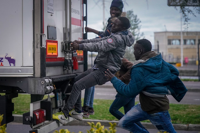 Migrants try to board a truck at Ouistreham ferry port in the hope of reaching the UK on September 12, 2018 in Ouistreham, France. After the clamp down at Calais many young migrants are seeking out new routes to the United Kingdom as stowaways on vehicles making the channel crossing by ferry from French ports. The migrants, of mostly African origin, camp out on the roadside and woodland areas as the authorities prevent the setting up of any camps. (Photo by Christopher Furlong/Getty Images)
