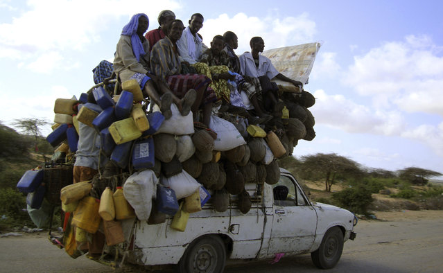 Residents ride on a pick-up truck that supplies milk and other items in Somalia's capital Mogadishu, September 2, 2009. (Photo by Omar Faruk/Reuters)