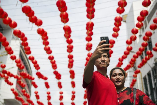A man and woman wearing traditional red clothes celebrating the Chinese Lunar New Year take pictures of themselves in Bangkok February 19, 2015. (Photo by Damir Sagolj/Reuters)