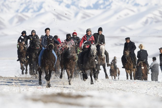 Herders ride horses during a race at a winter festival in Yining, Xinjiang Uighur Autonomous Region, China, January 10, 2016. The Kazakh festival included games such as Buzkashi, horse racing, wrestling and Kyz Kuu (catch the girl), according to local media. (Photo by Reuters/China Daily)