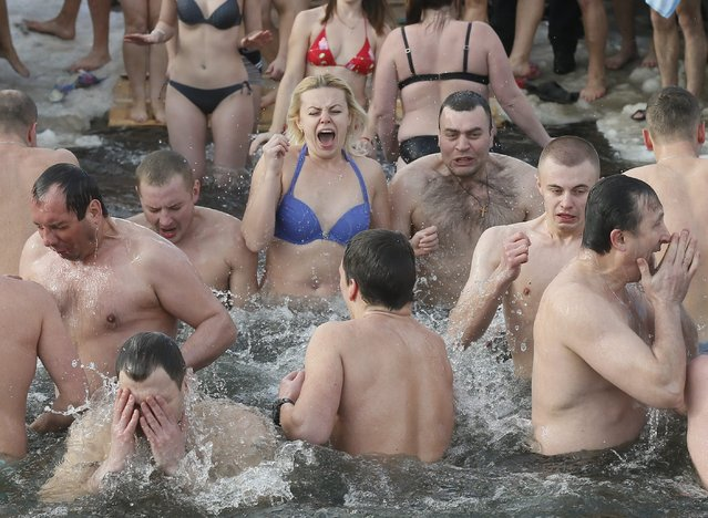 Orthodox believers bathe in cold water during Epiphany celebrations in Kiev, Ukraine, 19 January 2016. During Epiphany, some people believe that the waters have special curative properties and can be used to treat various illnesses, and many of them take icy baths as part of its celebration. (Photo by Sergey Dolzhenko/EPA)