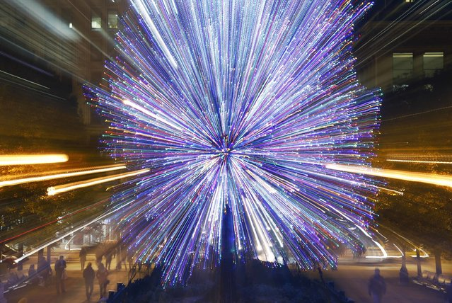Tourists walk past the Millennium Park Christmas tree in a timed exposure with a zoom lens Wednesday, November 30, 2016, in Chicago. (Photo by Charles Rex Arbogast/AP Photo)