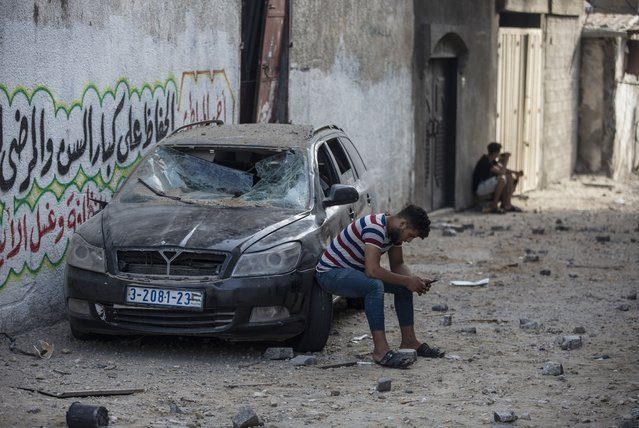 A Palestinian man sits on a damaged car following Israeli airstrikes on Jabaliya refugee camp, northern Gaza Strip, Thursday, May 20, 2021. Heavy airstrikes pummeled a street in the Jabaliya refugee camp in northern Gaza, destroying ramshackle homes with corrugated metal roofs nearby. The military said it struck two underground launchers in the camp used to fire rockets at Tel Aviv. (Photo by Khalil Hamra/AP Photo)