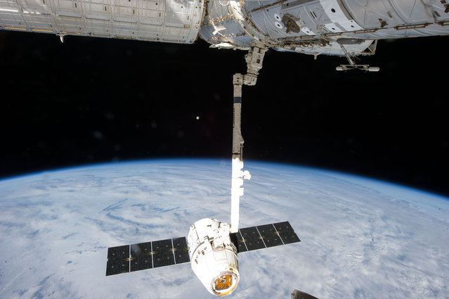 This image provided by NASA is one of a series of still photos documenting the process to release the SpaceX Dragon-2 spacecraft from the International Space Station, on March 26, 2013. The spacecraft, filled with experiments and old supplies, can be seen in the grasp of the Space Station Remote Manipulator System's robot arm or CanadArm2 after it was undocked from the orbital outpost. The Dragon was scheduled to make a landing in the Pacific Ocean, off the coast of California, later in the day. The moon can be seen at center. (Photo by AP Photo/NASA)
