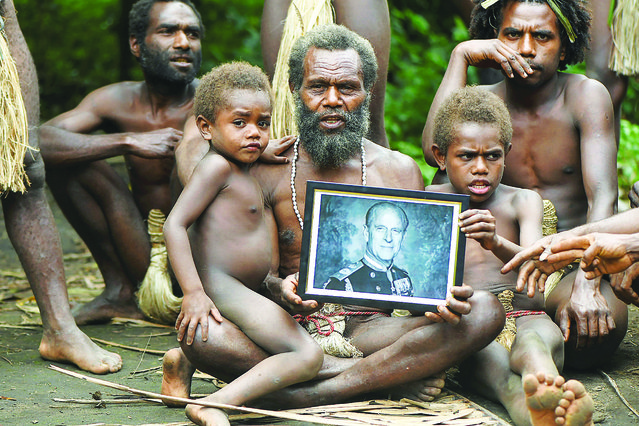 Yakel village chief Albi, and members of his family, holds a portrait of Britain's Prince Philip, Duke of Edinburgh, in the remote Pacific village of Vanuatu on April 12, 2021 as they worshipped Prince Philip as a living god. (Photo by Dan McGarry/AFP Photo)