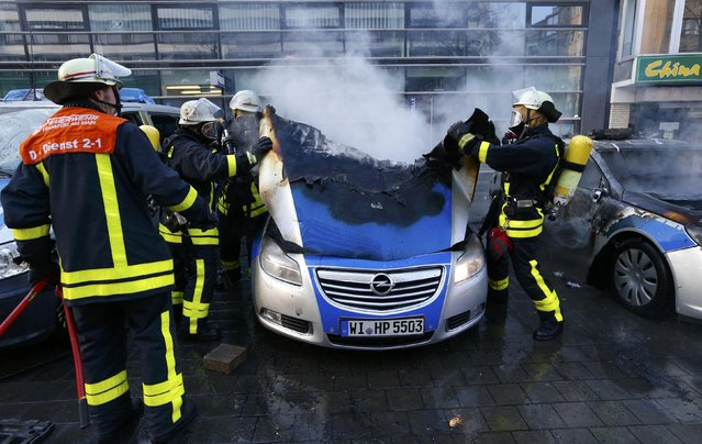 "Fireworkers extinguish police vehicles set of fire by anti-capitalist ""Blockupy"" protesters near the European Central Bank (ECB) building before the official opening of its new headquarters in Frankfurt March 18, 2015. (Photo by Ralph Orlowski/Reuters)"