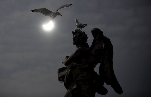 A partial solar eclipse is seen over a statue at the Mausoleum of Hadrian, usually known as Castel Sant'Angelo, in Rome March 20, 2015. (Photo by Yara Nardi/Reuters)