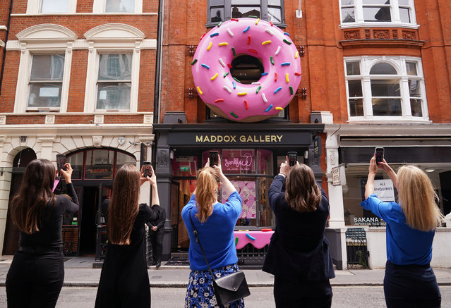 """A group of women take photos of a giant donut installation outside the Maddox Gallery in Mayfair, London on Thursday June 24, 2021, to celebrate a new exhibition entitled Villainy, a body of work by an anonymous street artist from New York who operates under the alias, """"Jerkface"""". (Photo by Yui Mok/PA Wire Press Association)"""