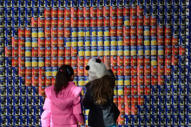 "School children look at a Superman logo made out of food cans during the 21st annual ""Canstruction"" exhibition and food drive in New York, November 4, 2013. (Photo by Emmanuel Dunand/AFP Photo)"