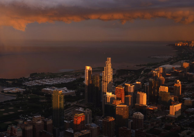 The shadow of the Willis Tower falls on Lake Michigan as the setting sun lights up low passing storm clouds, Tuesday, June 29, 2021, in Chicago. (Photo by Shafkat Anowar/AP Photo)
