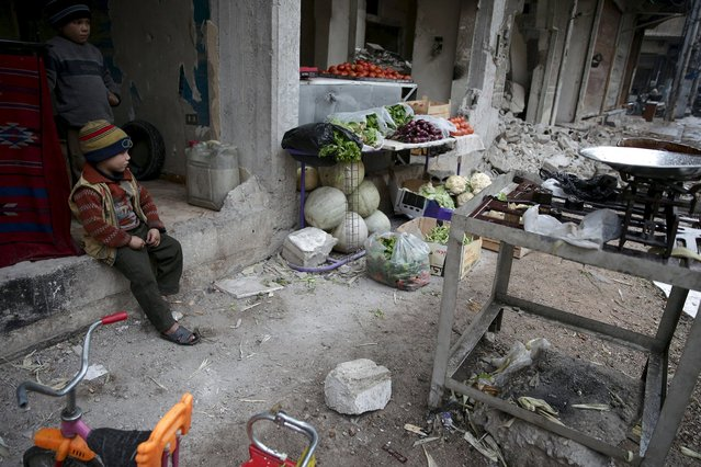 Children rest near produce displayed for sale in the town of Douma, eastern Ghouta in Damascus, Syria November 17, 2015. (Photo by Bassam Khabieh/Reuters)