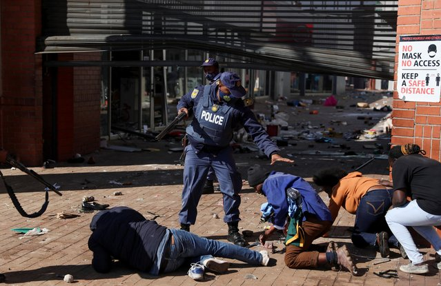 Police officers detain demonstrators as protests continue, following imprisonment of former South Africa President Jacob Zuma, in Katlehong, South Africa, July 12, 2021. (Photo by Siphiwe Sibeko/Reuters)