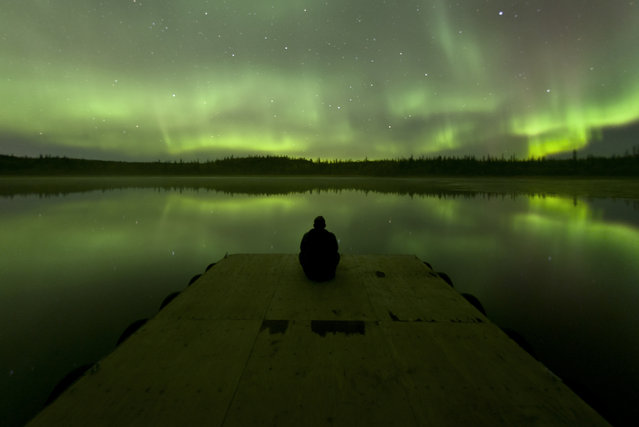 """Stargazing on the Dock"". I had to hold pretty still for this shot, but thankfully the water stayed calm and the sky gave me quite a light show. Photo location: Yellowknife, Northwest Territories, Canada. (Photo and caption by Ben Leshchinsky/National Geographic Photo Contest)"