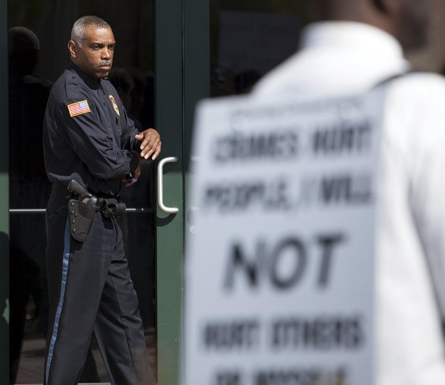 A police officer watches protestors at a rally in North Charleston, South Carolina April 8, 2015. (Photo by Randall Hill/Reuters)