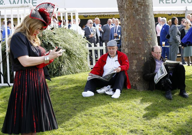 Horse Racing – Crabbie's Grand National Festival – Aintree Racecourse April 10, 2015: A man looks at a fellow racegoer on ladies day during the Grand National. (Photo by Darren Staples/Reuters)