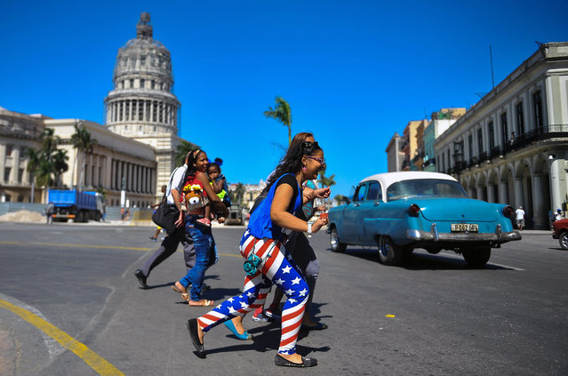 A woman wearing leggings with the colours of the US flag walks along a street of Havana on February 18, 2015. President Barack Obama announced Thursday he will make a landmark visit to Cuba on March 21-22, pledging to address human rights as America pursues a historic thaw with its former Cold War foe. (Photo by Yamil Lage/AFP Photo)