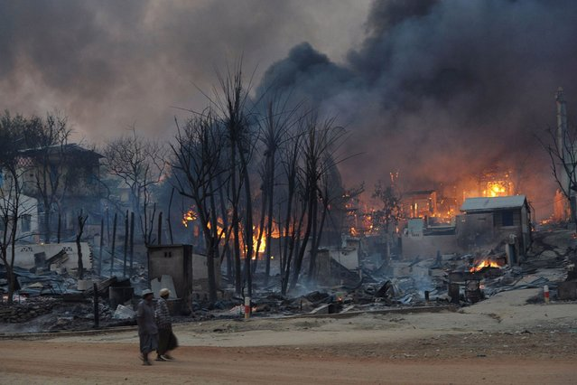 Residents walk past buildings burning in riot-hit Meiktila, central Myanmar on March 21, 2013. (Photo by Soe Than Win/AFP Photo)