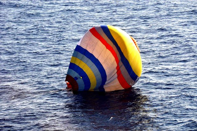This handout picture taken by the Japan Coast Guard on January 1, 2014 shows a hot air balloon which was carrying a Chinese man as it lands on the water, south of the disputed islets known as the Senkaku islands in Japan and Diaoyu islands in China, in the East China Sea. (Photo by AFP Photo/Japan Coast Guard)