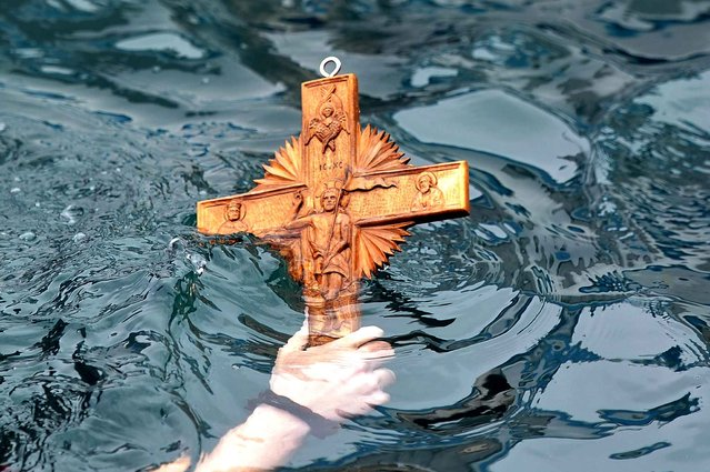 A man retrieves a wooden cross from the sea during the ceremony of the blessing of the waters marking the orthodox Epiphany Day at the port of Aiegina island near Athens on January 6, 2014. (Photo by Louisa Gouliamaki/AFP Photo)