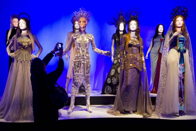 A visitor takes pictures of creations during the press visit of the Jean Paul Gaultier Exhibition at the Grand Palais in Paris, March 30, 2015. The Jean Paul Gaultier fashion exhibition, which will take place from April 1 to August 3, 2015, will present 175 Haute Couture and ready-to-wear outfits designed between 1976 and 2015. (Photo by Charles Platiau/Reuters)