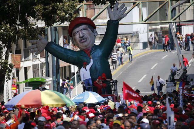 An inflatable doll depicting Venezuela's late President Hugo Chavez stands outside of Miraflores presidential palace, during a march of in defense of the state-run oil company PDVSA, in Caracas, Venezuela, Thursday, January 31, 2019. The government called for a mass rally to denounce U.S. sanctions against PDVSA that could starve Maduro's government of billions in export revenue but turnout was no more than a few hundred people. (Photo by Ariana Cubillos/AP Photo)
