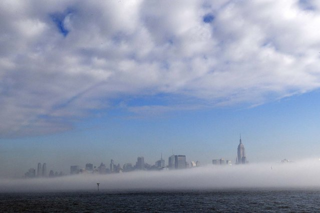 Parts of the New York City skyline peek through thick fog in this view from Pier A Park in Hoboken, N.J. (Photo by Julio Cortez/Associated Press)