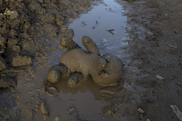 A doll lies in the mud  at a refugee camp in the northern Greek border station of Idomeni on, Tuesday, March, 1 2016. Some 7,000 migrants, including many from Syria and Iraq, are crammed into a tiny camp at the Greek border village of Idomeni, and hundreds more are arriving daily. (Photo by Petros Giannakouris/AP Photo)