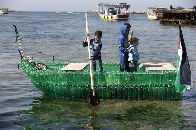 Palestinian children pose for a picture on a makeshift boat made of plastic bottles on April 18, 2015 at the port of Gaza City. (Photo by Mohammed Abed/AFP Photo)