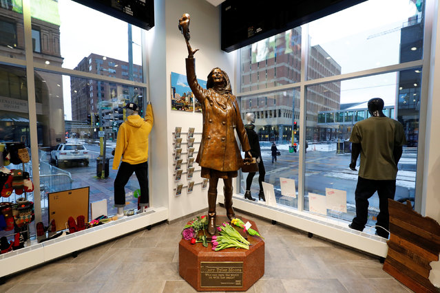"""Flowers lay at a bronze sculpture depicting actress Mary Tyler Moore from the opening credits of the television sitcom """"The Mary Tyler Moore Show"""" in Minneapolis, Minnesota, U.S., January 25, 2017. (Photo by Adam Bettcher/Reuters)"""