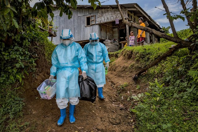 Healthcare workers wearing hazmat suits visit houses to conduct swab tests on residents exposed to COVID-19 patients on September 6, 2021 in the mountainous village of Basca in Aringay town, La Union province, Philippines. Healthcare workers from the Aringay COVID-19 Diagnostic Team often have to go on long walks to reach remote villages in their town to conduct contact tracing on suspected COVID-19 patients. Due to a lack of supply of protective equipment from the country's health department, they are forced to wear their hazmat suits as they cross rivers and mountains under the scorching sun or intense rain to avoid wastage. The country is struggling to cope with a huge wave of cases fueled by the more infectious Delta variant, recording more than 2 million cases and more than 34,000 deaths with every one in four people tested turning out positive for the coronavirus. (Photo by Ezra Acayan/Getty Images)