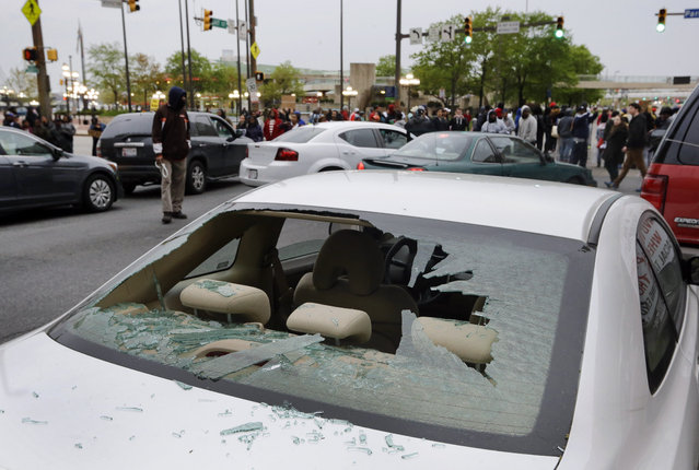 A car with a broken window sits near an intersection full of protestors after a rally for Freddie Gray, Saturday, April 25, 2015, in Baltimore. (Photo by Patrick Semansky/AP Photo)