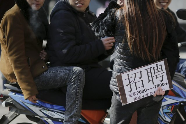 A recruiter holding a placard advertising jobs talks to young men at an unofficial job market in suburbs of Beijing, China February 24, 2016. A whole generation of Chinese youth raised in a miracle economy over the past decade tilt headlong into a period of material uncertainty as jobs come less easily. As China's annual parliament sessions kick off next month, the Communist Party will unveil its Five-Year Plan widely expected to outline additional measures to help create jobs and strategies to soothe the sting of massive layoffs as the economy corrects its past excesses and moves away from traditional heavy industries such as coal and steel. (Photo by Damir Sagolj/Reuters)