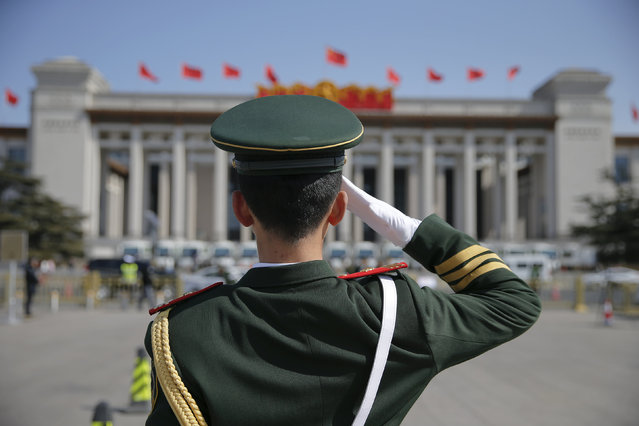 A paramilitary policeman salutes towards China's National Museum during the second plenary session of the National People's Congress (NPC) at the Tiananmen Square in Beijing, China, March 9, 2016. (Photo by Damir Sagolj/Reuters)